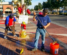 Good Samaritans: Locals clean the Thomas memorial in the aftermath of vandalism on Commonwealth Ave. in Fullerton. Photo by Josa Lamont