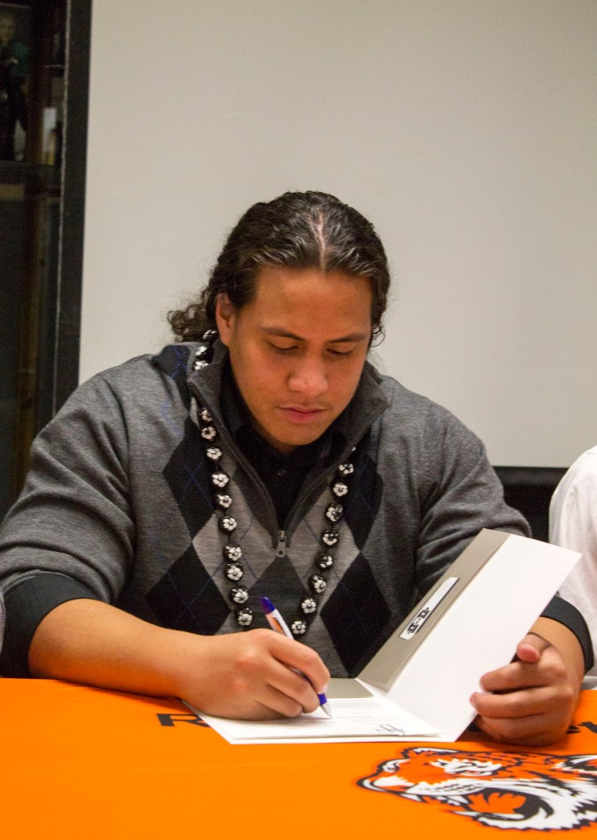 Signed: Tigers' Edmund Faimalo signs his letter of intent to play football at Utah State on Feb. 6 in RCC's Hall of Fame Room(Photo by Luis Solis)