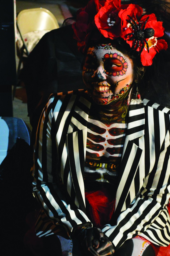 "Rebekah Josoh warms up in the cool evening of  Dia de los Muertos in a striped jacket reminiscent of the undead character in Tim Burton's ""Beetlejuice"""