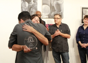 Carla Conti, photography instructor, hugs Hugo Fernando while presenting a Student Honors Award at the Student Honors Exhibition 2016 reception and award ceremony May 5.