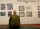 Steve Gregg, husband of art professor Dayna Mason Gregg, sits and looks at art in the Student Honors Exhibition 2016 May 5.