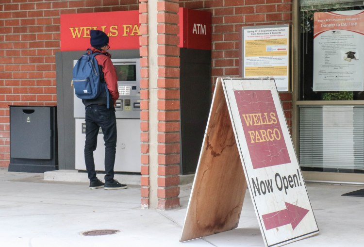 An RCC student withdraws cash at the Wells Fargo ATM machine outside the Cesar Chavez Building